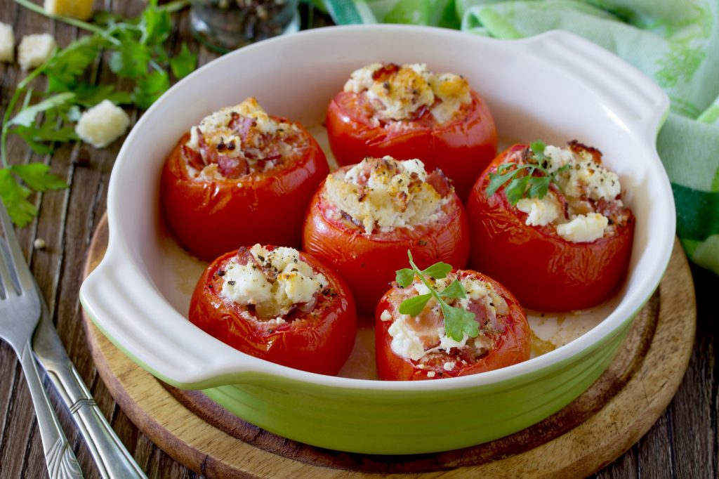 Baked stuffed tomatoes with bacon and feta cheese on a wooden ta