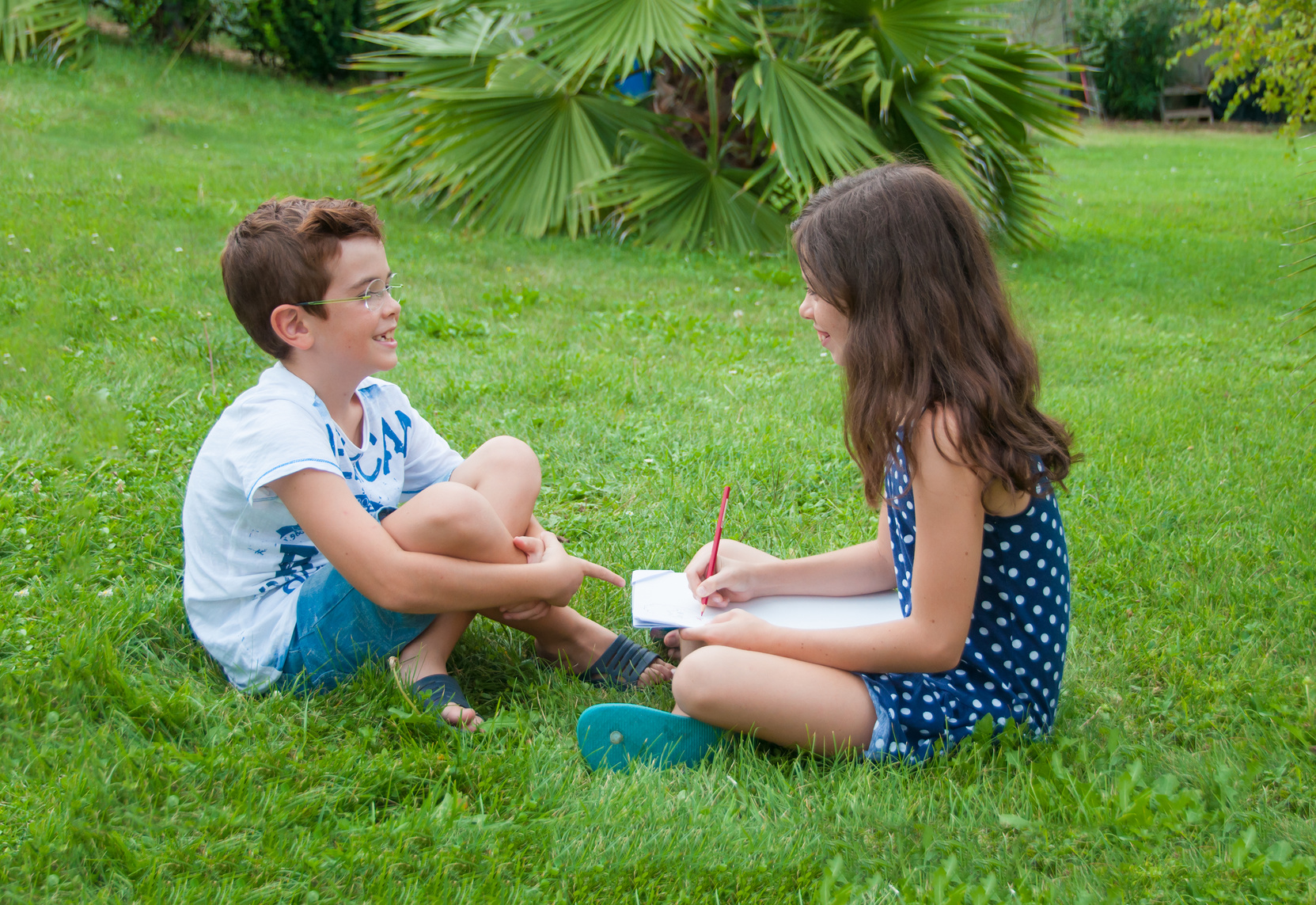 Girl drawing her brother outdoors on grass in summer