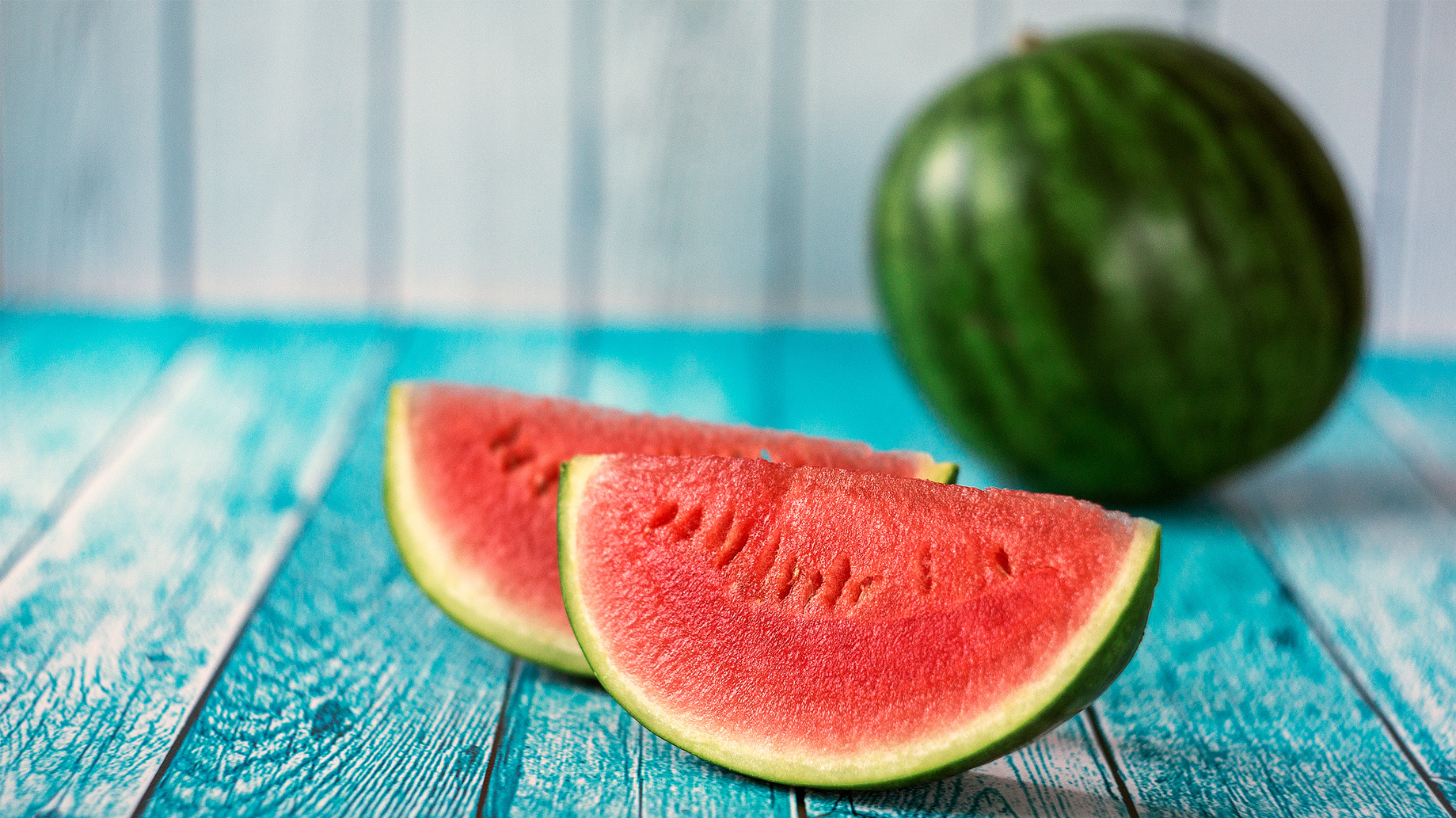 Watermelon slice popsicles on a blue rustic wood background. Selective focus