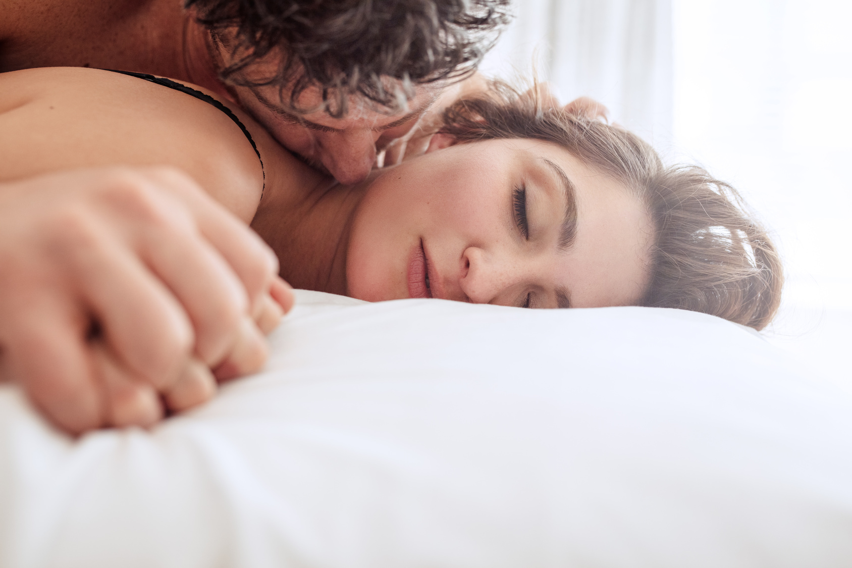 Romantic young couple making love in bed