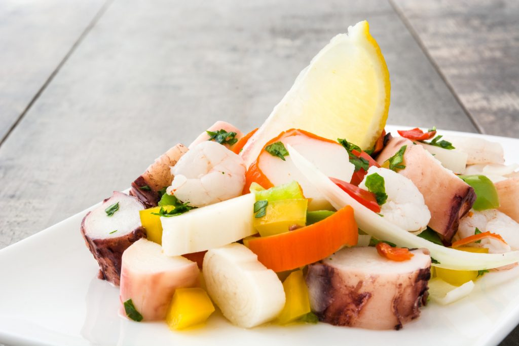 Traditional seafood ceviche from Peru on wooden background