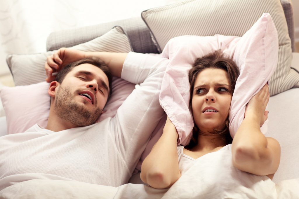 Angry woman in bed with snoring man